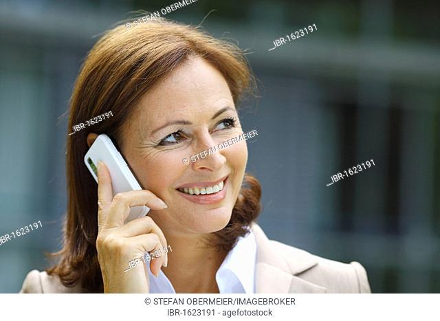 Business woman, 45 years, talking on a mobile phone
