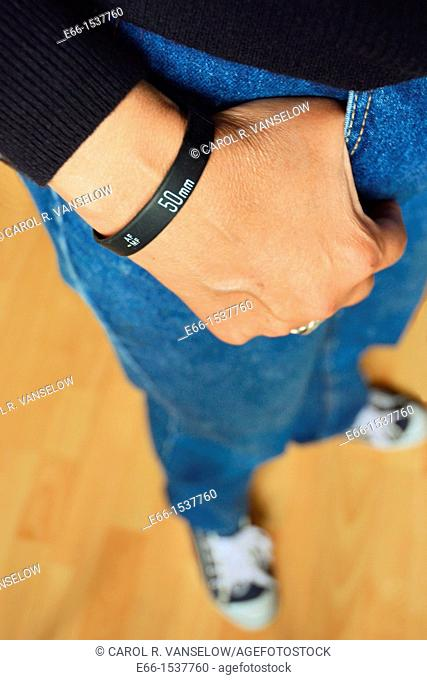 Woman in blue jeans, black sweater and sneakers, wearing a 'Lens Bracelet' designed by Adam Elmakais - with shallow depth of field