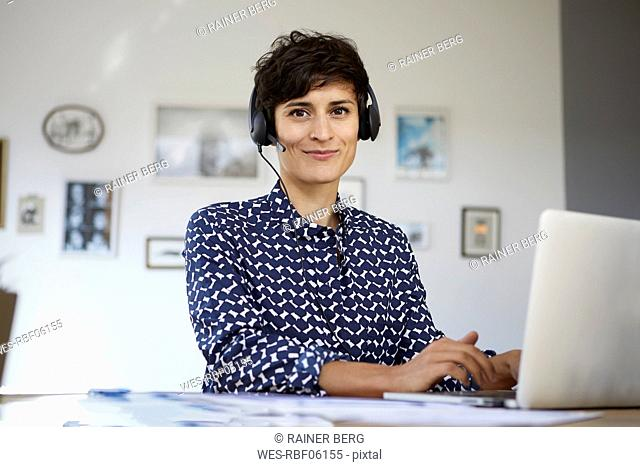 Portrait of smiling woman at home with headset and laptop