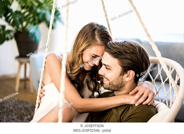 Happy affectionate couple embracing in hanging chair at home