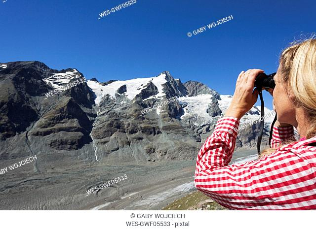 Austria, Carinthia, woman looking through binoculars pointing at GroÇ.glockner peak and Pasterze glacier, view from Kaiser-Franz-Josefs-Hoehe