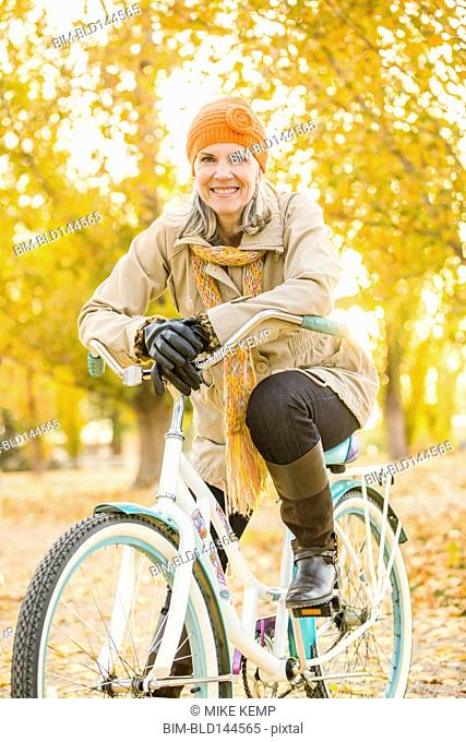 Older Caucasian woman riding bicycle on autumn leaves