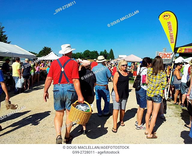A man with suspenders, a red shirt and short pants carries a basket through a crowd of people at a weekly market held on a farm in a rural part of Ontario