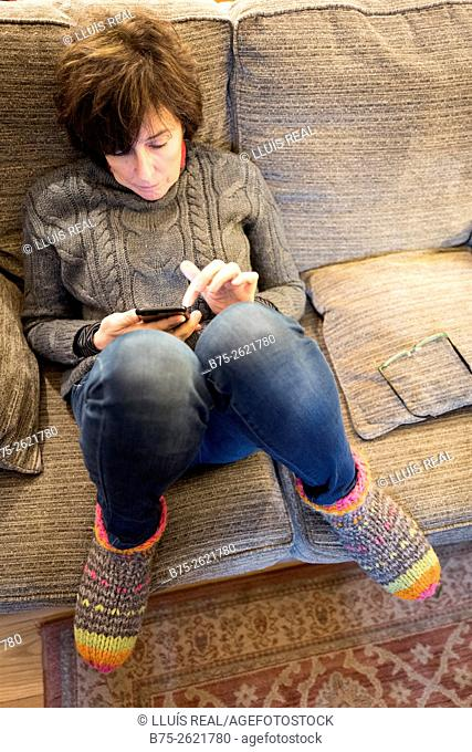 Closeup of a woman sitting on fitness informal and relaxed on a couch, manipulating a cell phone. Buckden, Skipton, Yorkshire Dales, England, UK, Europe