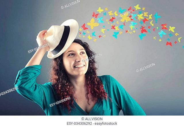 Portrait of beautiful girl with hat over head and colorful butterflies flies away