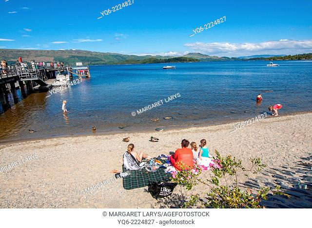 Luss, Loch Lomond and the beach with people swimming and sunbathing on a lovely summer day