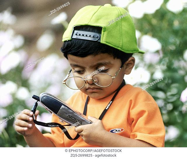 A little boy wearing a cap and spectacles plays with a cell phone