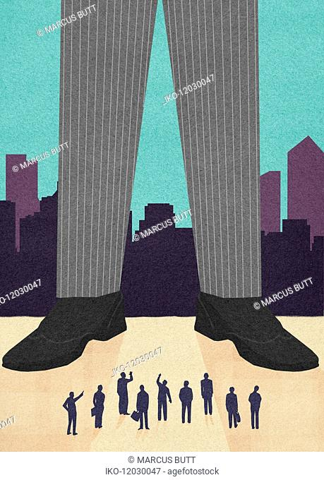 Small businessmen looking up at legs of tall businessman