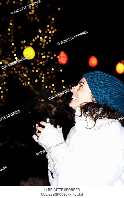 Woman holding cup watching the night sky