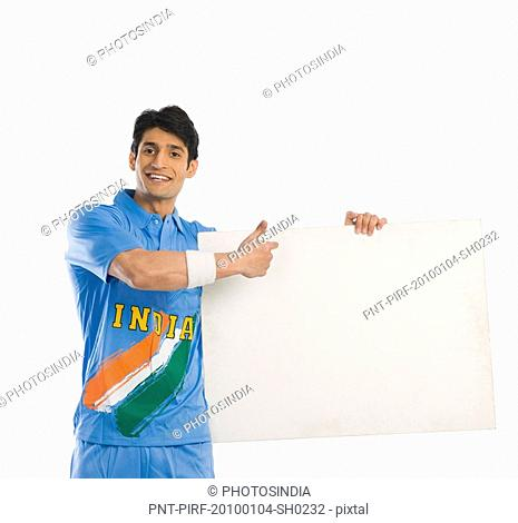 Cricket player pointing at a blank placard and smiling