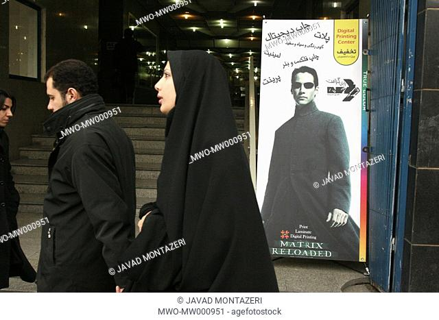 Iranian couple passes in front of US actor Keanu Reeves banner which uses for a digital printing store advertising in center of Tehran capital city