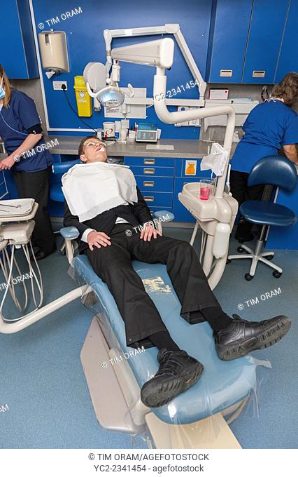 A 14 year old boy having a tooth extracted at the dentists in the Uk