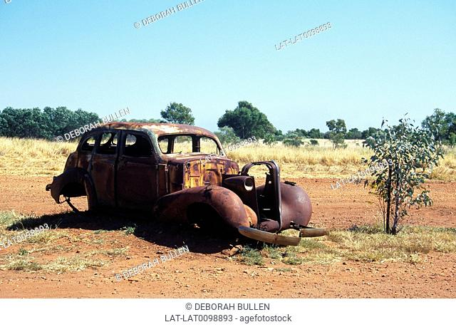 Old rusted burnt out car. In outback. Red dust. Scrub vegetation