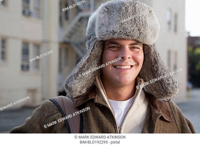 Mixed race man wearing fur hat