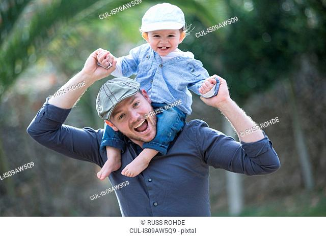 Baby boy wearing baseball cap sitting on father shoulders looking at camera smiling
