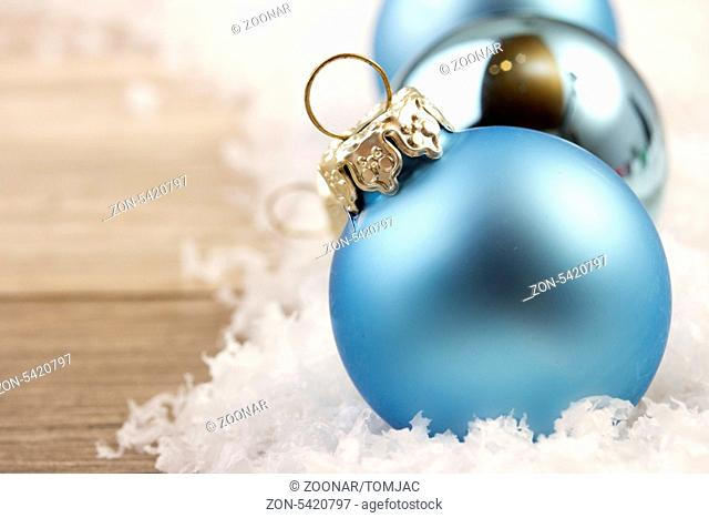christmas decoration with wooden background, snow, christmas baubles blue and silver