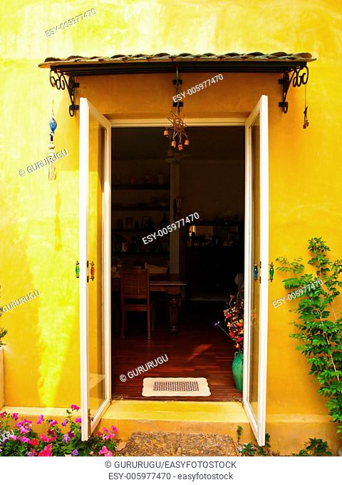 Yellow house wall with opened door and flower