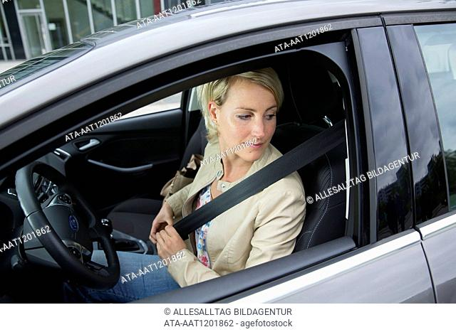 Female car driver buckles up her seatbelt