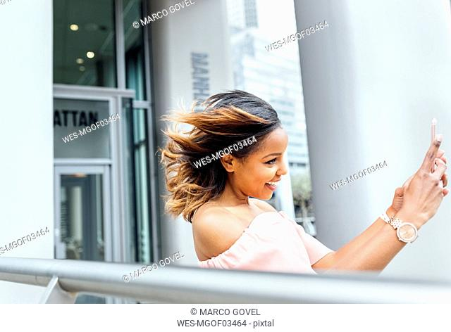 Smiling woman taking a selfie in the city
