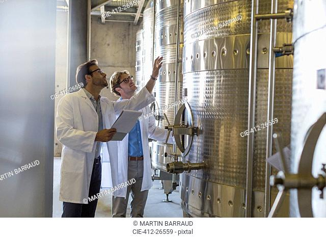 Vintners in lab coats checking vats in winery cellar