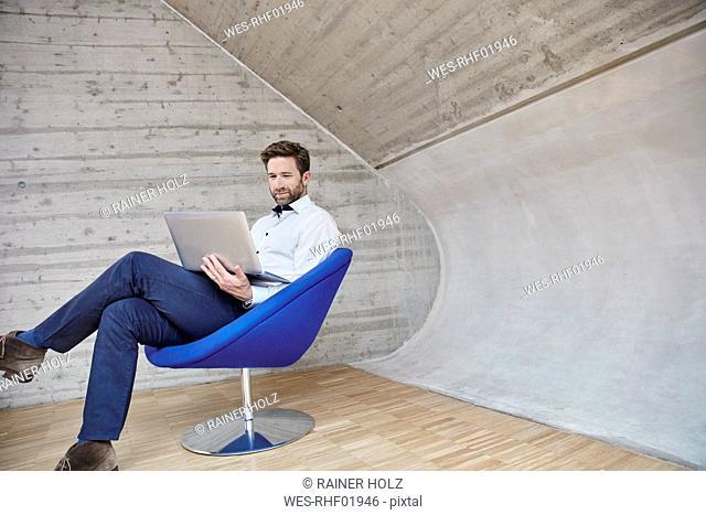 Businessman sitting on chair using laptop