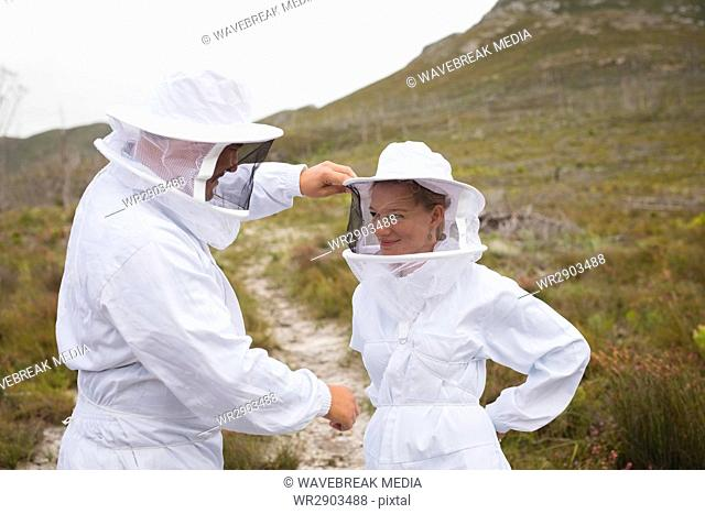 Beekeeper adjusting hat of female colleague at field