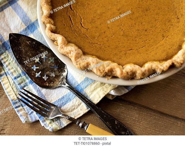 Pumpkin pie on cloth with old fashioned cutlery on wood