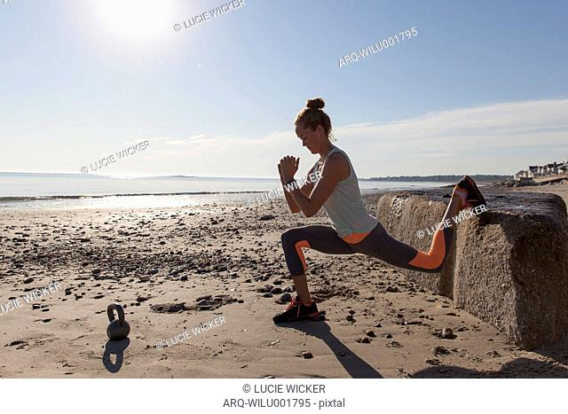 Woman Doing Stretching On Beach