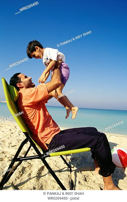A father holds his son while seated on the chair as they enjoy at the beach