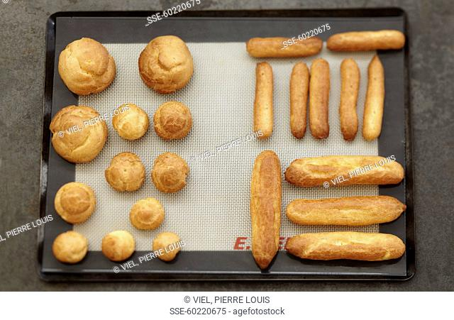 Pastry puffs and pastry for Eclairs on a baking sheet just taken out of the oven