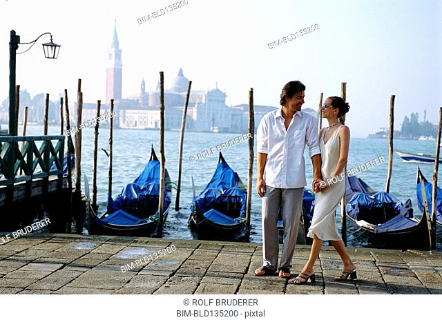 Couple holding hands on urban canal front, Venice, Veneto, Italy