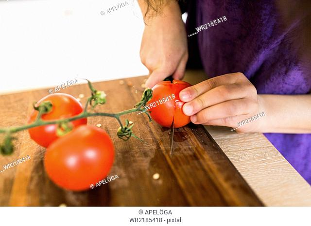 Cropped image of girl slicing tomatoes on cutting board in kitchen