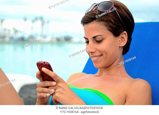 Young attractive woman using mobile telephone in swimming pool