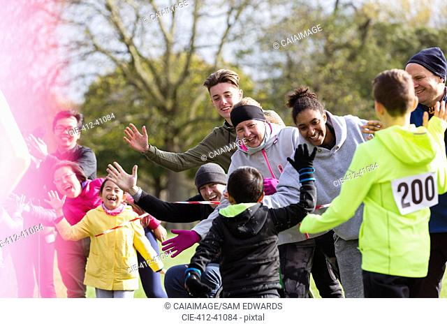 Spectators high-fiving runners at charity run in park