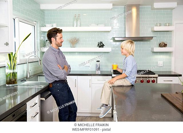 Father and son in kitchen with glass of orange juice