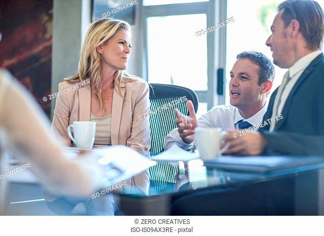 Businessmen and women holding team meeting at office desk