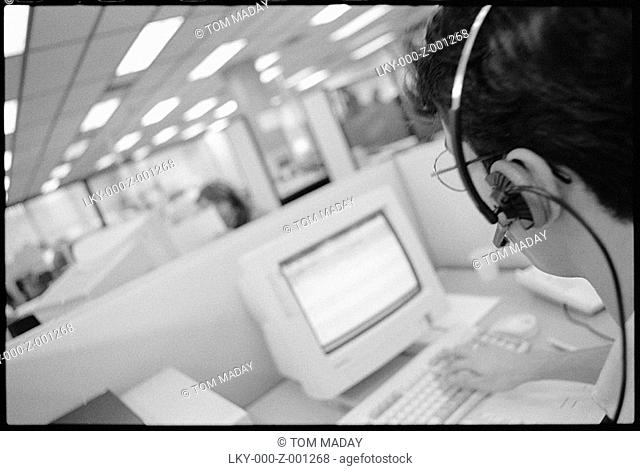 Telemarketer on hands-free phone in office
