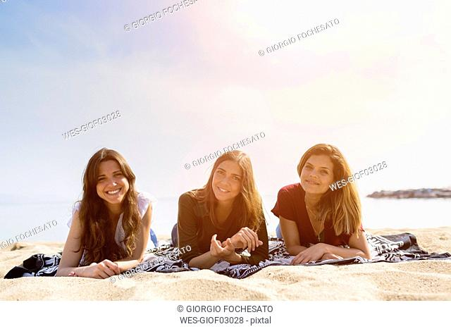 Portrait of three female friends relaxing on the beach