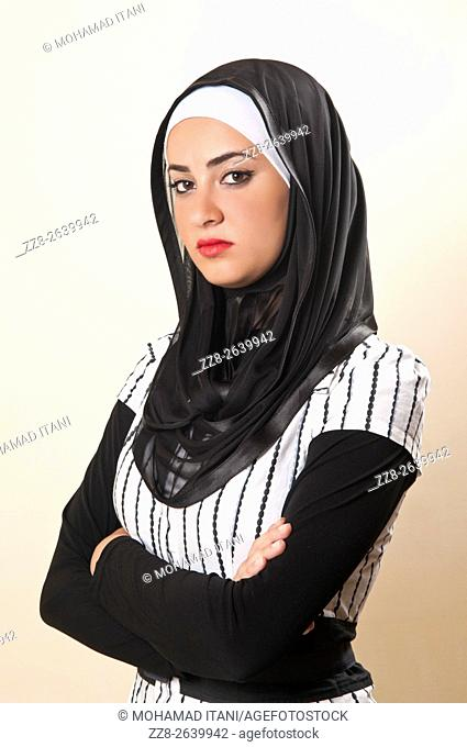 Unhappy young Muslim woman standing with arms folded