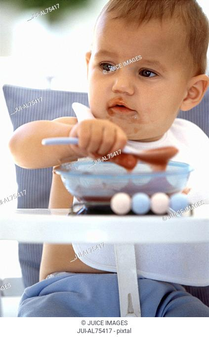 View of baby playing and eating in highchair