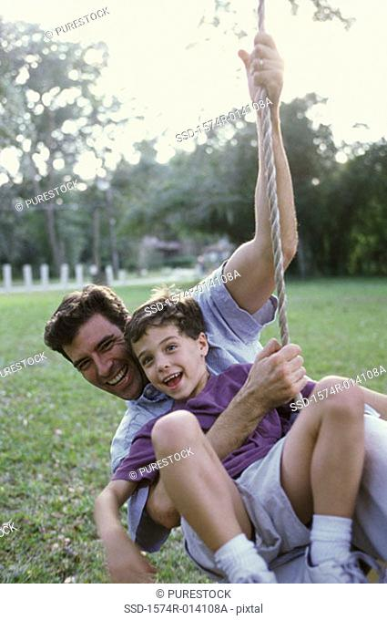 Father and son swinging on a rope swing