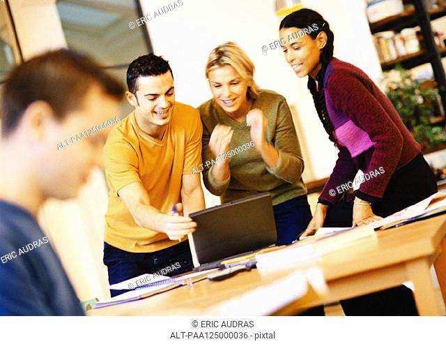 People in office, three people looking at laptop computer