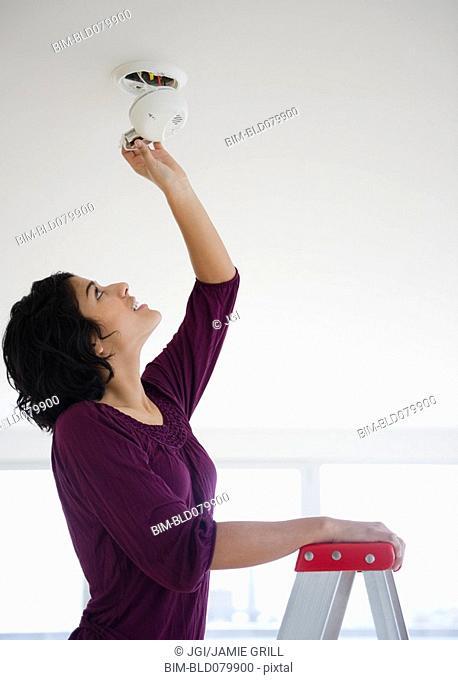 Hispanic woman fixing fire alarm