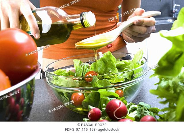 Mid section view of a woman pouring olive oil into a wooden spoon