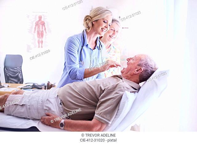 Doctor examining senior man's mouth at checkup