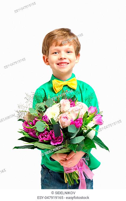 Nice photo of handsome little boy on white background. Boy smiling and holding big bouquet of flowers