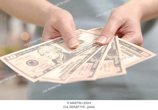 Female hands holding ten dollar notes
