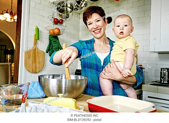 Caucasian mother cooking with baby in kitchen