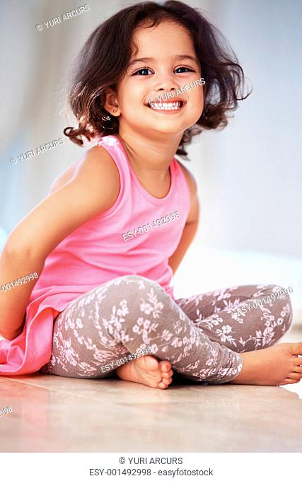Portrait of adorable little girl sitting on floor with cross legged and smiling