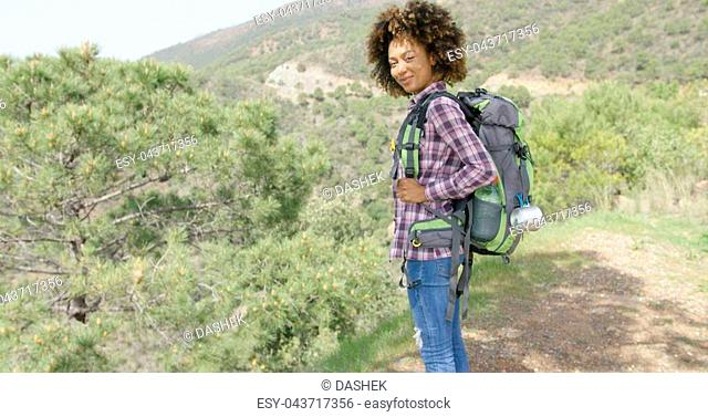 Young cheerful female in casual clothing with backpack standing on rural road on background of mountains alone